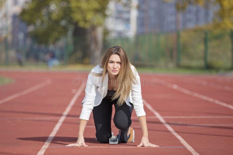 Bedrijfsvrouw in beginpositie klaar te lopen en sprint op atletiek het rennen spoor royalty-vrije stock afbeelding