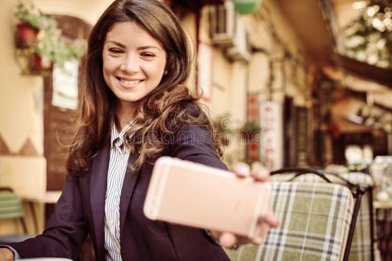 Bedrijfsvrouw bij koffie die een zelfportret met slimme telefoon nemen royalty-vrije stock afbeelding