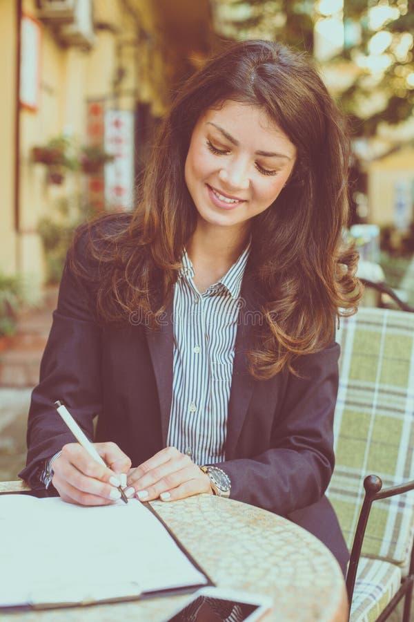 Bedrijfsvrouw bij koffie het schrijven documenten royalty-vrije stock fotografie