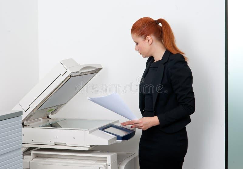 Bedrijfsvrouw die aan bureauprinter werkt royalty-vrije stock foto's