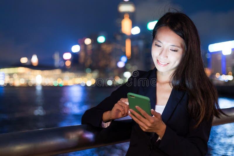 Bedrijfsvrouw die aan cellphone bij nacht werken stock foto's