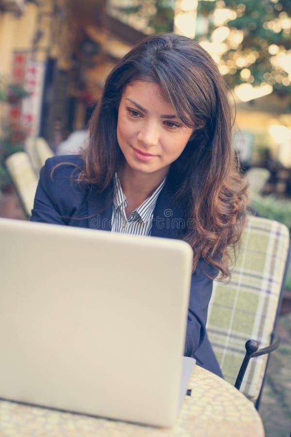 Bedrijfsvrouw die aan laptop bij koffie werken royalty-vrije stock fotografie