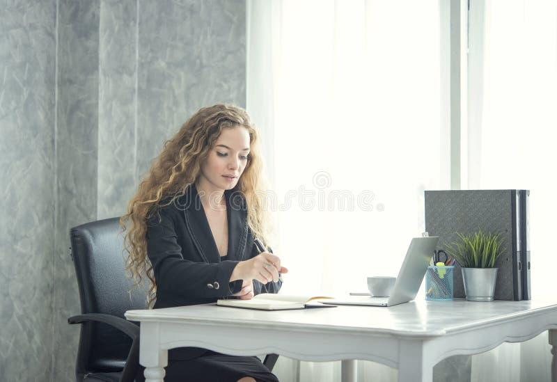Bedrijfsvrouw die bij bureau in haar bureau werken royalty-vrije stock foto