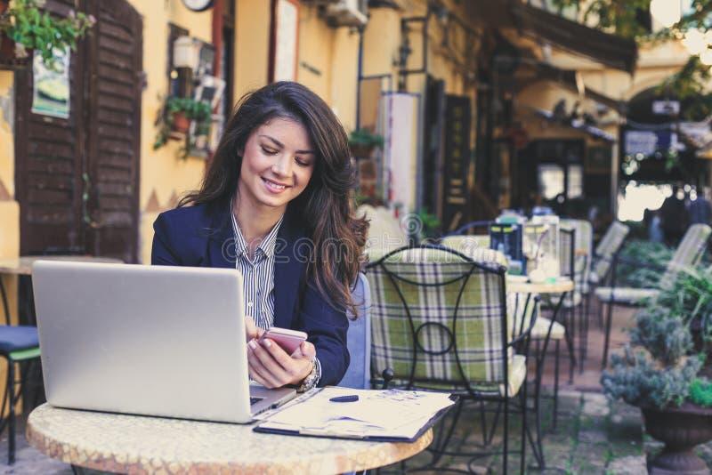 Bedrijfsvrouw die bij koffie aan laptop werken die slimme telefoon met behulp van stock fotografie