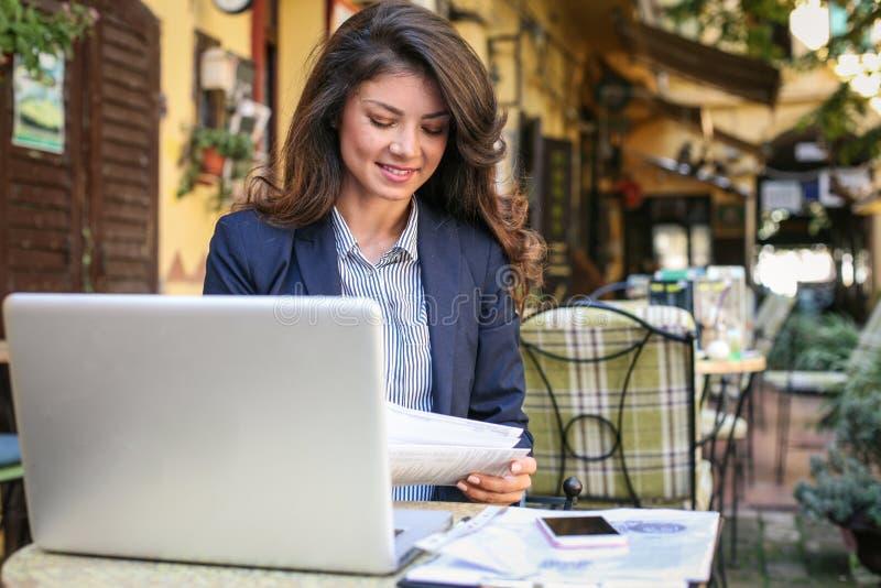 Bedrijfsvrouw die bij koffie werken die technologie gebruiken stock afbeeldingen
