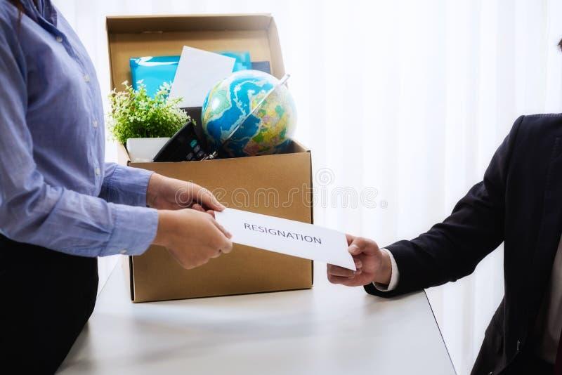 Bedrijfsvrouw die brief voor berusting verzenden naar werkgever met kartonvakje in bureau op kantoor Het concept treedt indrukt e stock afbeeldingen