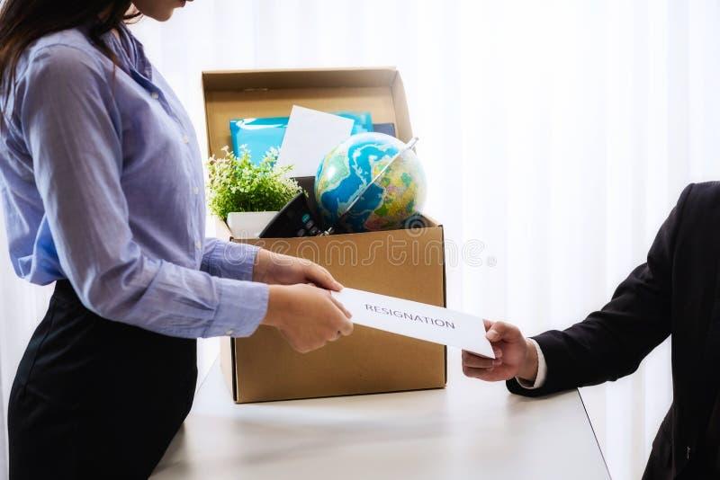 Bedrijfsvrouw die brief voor berusting verzenden naar werkgever met kartonvakje in bureau op kantoor Het concept treedt indrukt e stock afbeelding