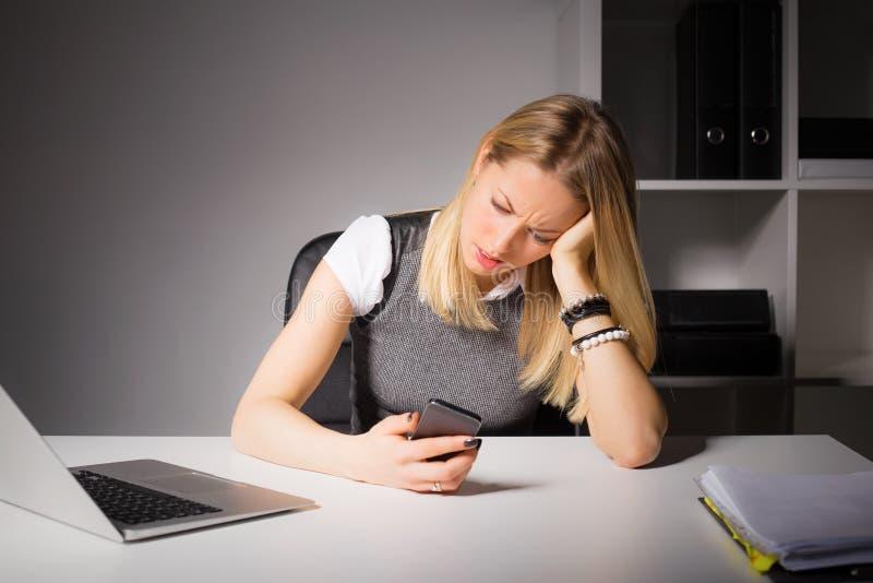 Bedrijfsvrouw die in bureau haar slimme telefoon bekijken royalty-vrije stock foto
