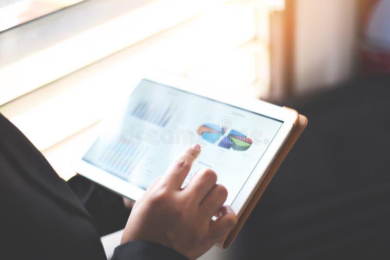 Bedrijfsvrouw die in bureau met het controleren van bedrijfsrapport in een tablet die - een tabletcomputer met behulp van geld we stock afbeeldingen