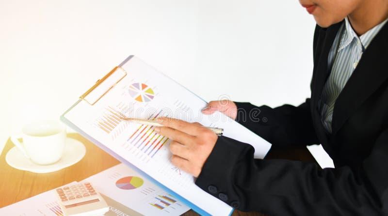 Bedrijfsvrouw die in bureau met het controleren van bedrijfsrapport over het lijstbureau werken met calculator en koffiekop die - stock afbeeldingen