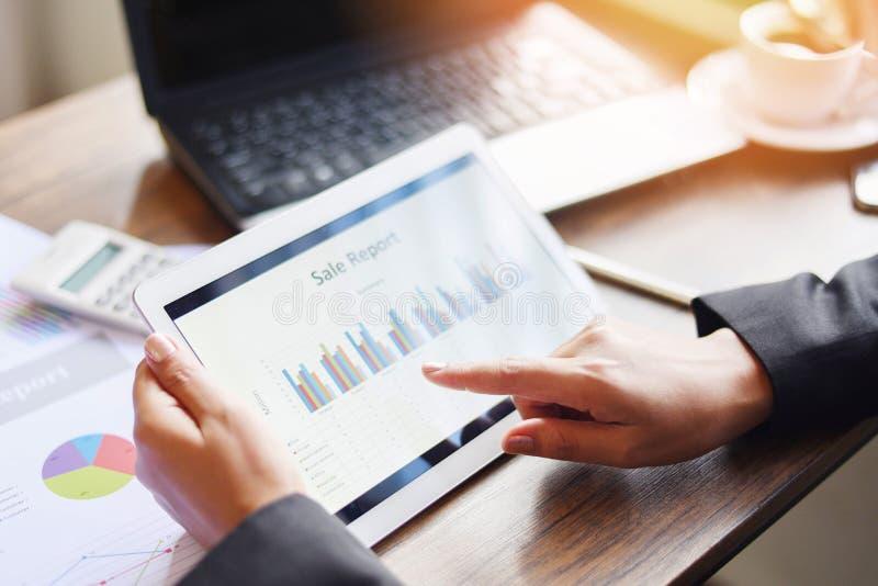 Bedrijfsvrouw die in bureau met het controleren van bedrijfsrapport werken die laptop van de tabletcomputertechnologie met calcul stock afbeelding