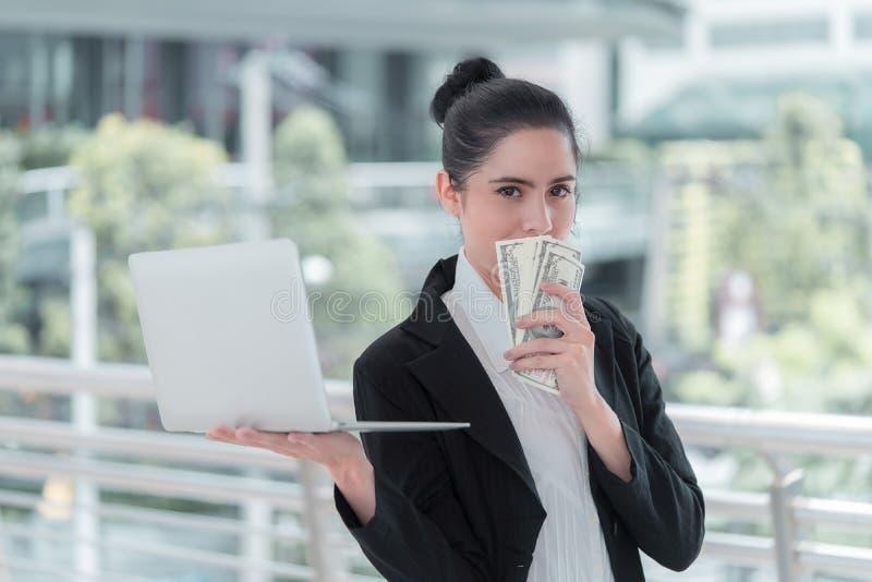 Bedrijfsvrouw die contant geld maken op laptop online stock afbeeldingen