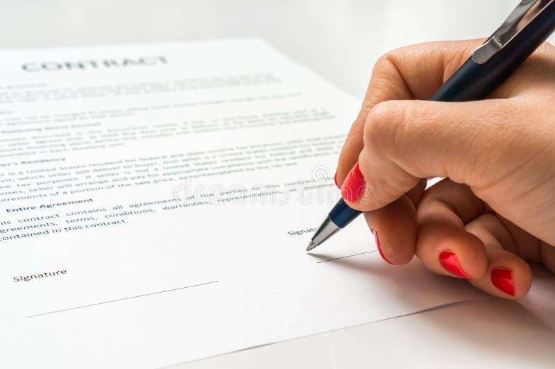 Bedrijfsvrouw die contractdocument in bureau ondertekenen royalty-vrije stock afbeelding