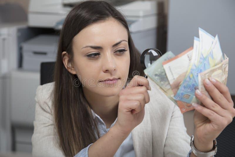 Bedrijfsvrouw die de authenticiteit van geld controleren stock fotografie