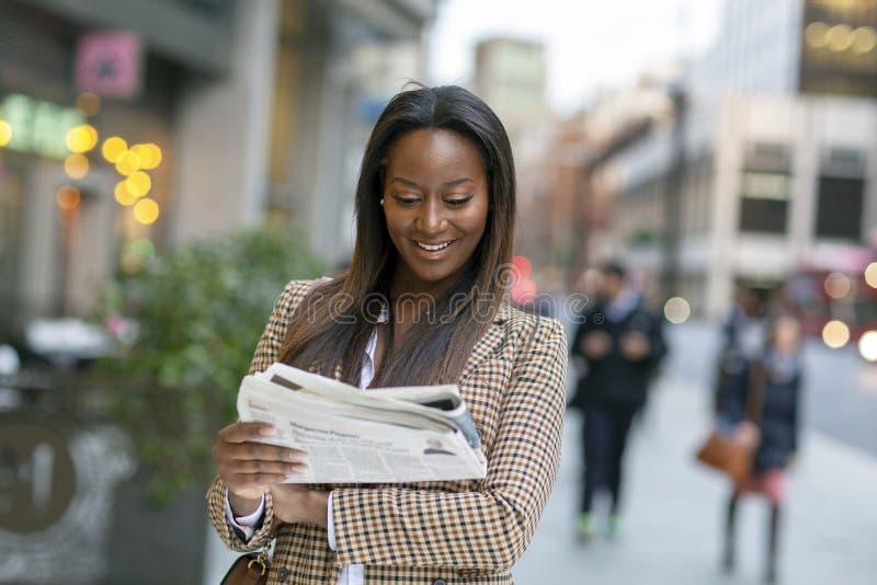 Bedrijfsvrouw die de krantekoppen lezen royalty-vrije stock fotografie