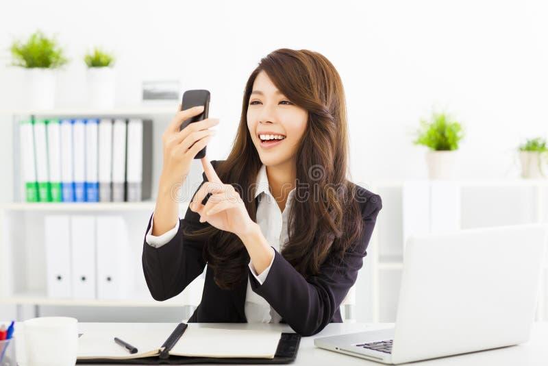 bedrijfsvrouw die de slimme telefoon in bureau met behulp van royalty-vrije stock foto