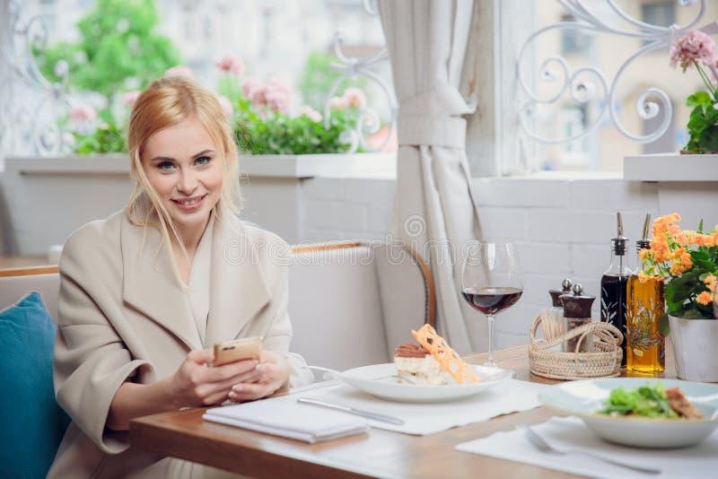 Bedrijfsvrouw die de slimme telefoon in een restaurant met behulp van stock foto's