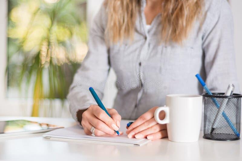 Bedrijfsvrouw die in document met pen bij bureau in modern bureau schrijven stock fotografie