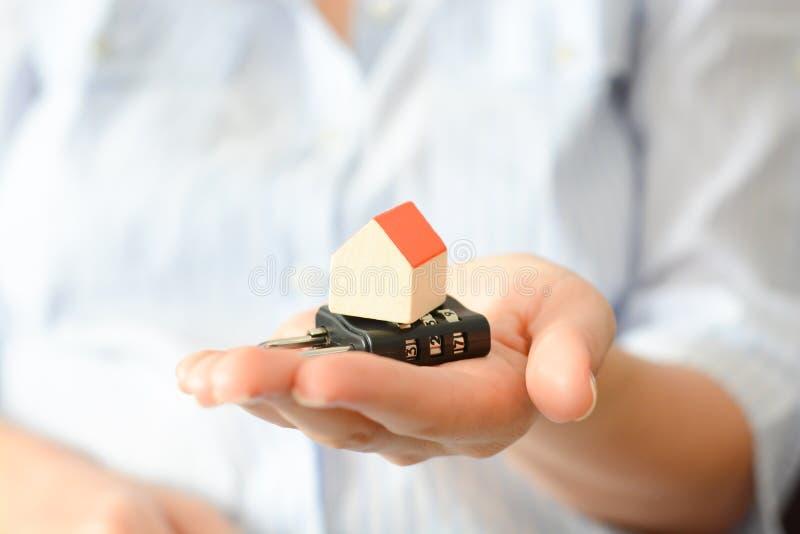 Bedrijfsvrouw die een cijferslot houden onder een miniatuurhuis, die het concept huisveiligheid of verzekering symboliseren stock foto's