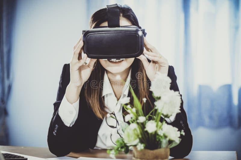 Bedrijfsvrouw die een VR-hoofdtelefoon voor het werk met virtuele werkelijkheid, met pret en gelukkige nieuwe ervaring, Concept m royalty-vrije stock afbeelding