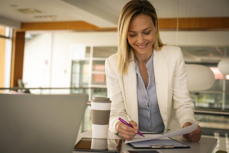 Bedrijfsvrouw die en het contract lezen ondertekenen op het kantoor royalty-vrije stock foto's