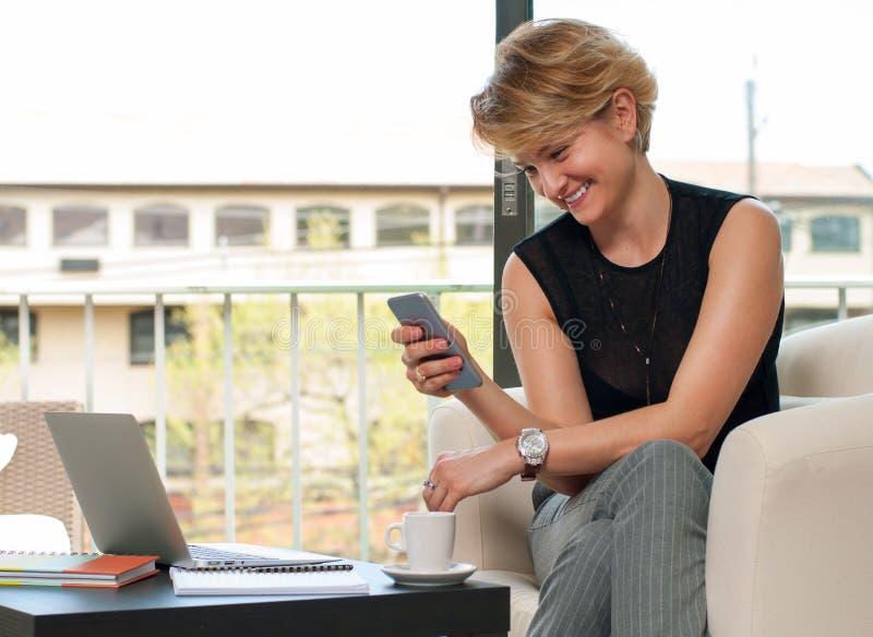 Bedrijfsvrouw die en slimme telefoon zitten met behulp van stock afbeelding