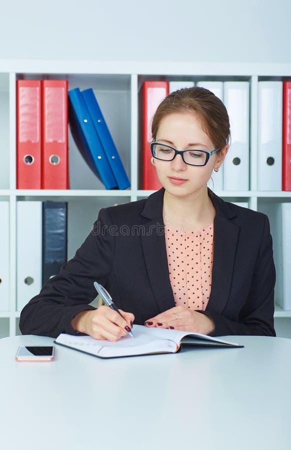 Bedrijfsvrouw die in glazen nota's maken op het bureauwerk De bedrijfsbaanaanbieding, financieel succes, verklaarde publiek royalty-vrije stock fotografie