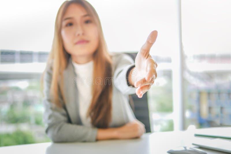 Bedrijfsvrouw die haar hand voor handdruk geven aan partner, het succesvolle concept van de vennootschapovereenkomst stock fotografie