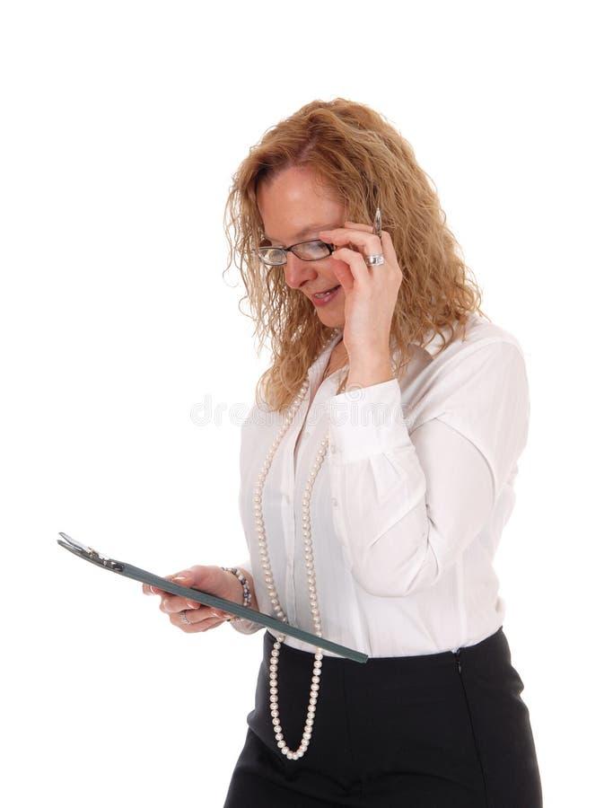 Bedrijfsvrouw die haar klembord bekijken royalty-vrije stock fotografie