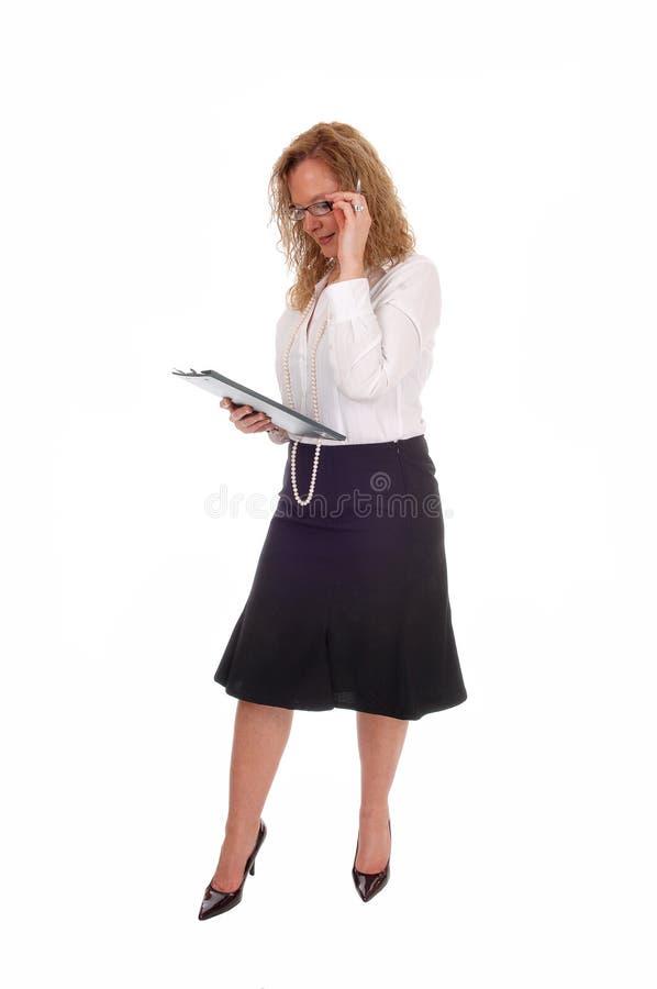 Bedrijfsvrouw die haar klembord bekijken stock fotografie