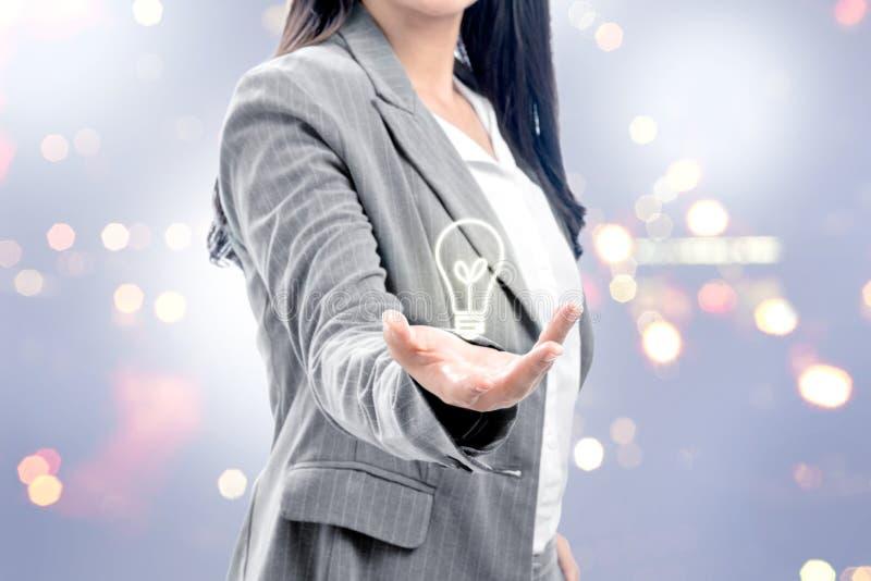 Bedrijfsvrouw die heldere gloeilamp in de handen tonen als symbool van innovatief idee royalty-vrije stock afbeelding
