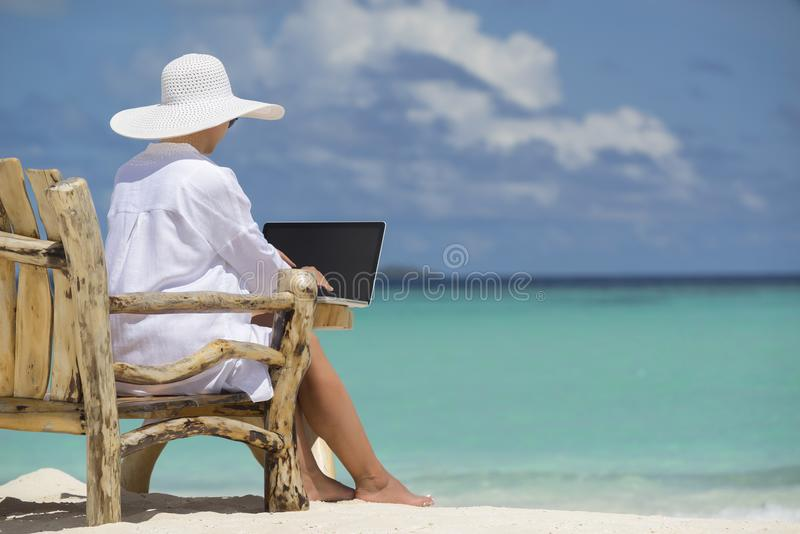 Bedrijfsvrouw die laptop computer op het strand met behulp van royalty-vrije stock fotografie