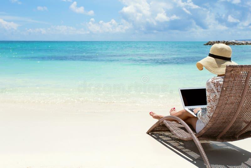 Bedrijfsvrouw die laptop computer op het strand met behulp van royalty-vrije stock afbeelding