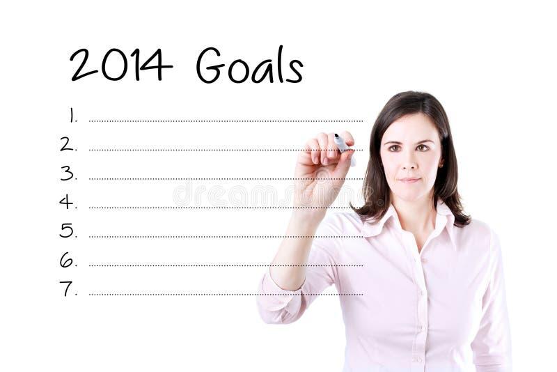 Bedrijfsvrouw die lege 2014 doelstellingen lijst schrijven stock afbeeldingen