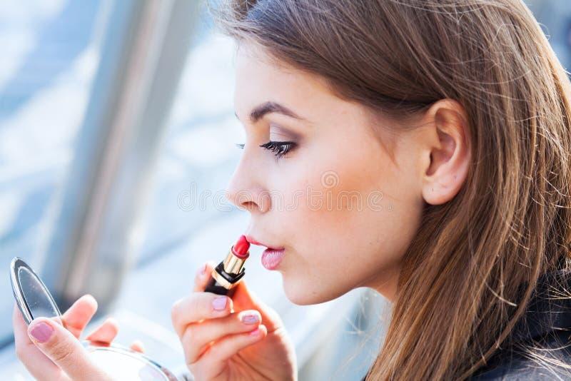 Bedrijfsvrouw die lippenstift gebruiken stock fotografie