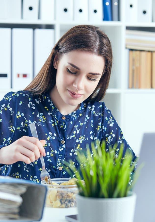 Bedrijfsvrouw die lunch eten op het haar werk die het laptop scherm bekijken Omslagen met documenten in de voorgrond royalty-vrije stock foto's