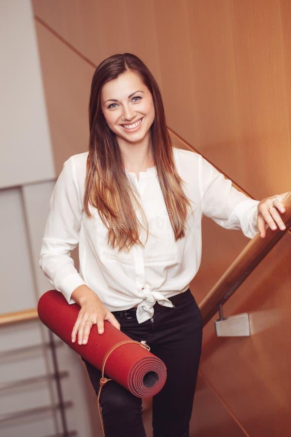 Bedrijfsvrouw die met blauwe ogen in wit blouseoverhemd en zwarte broek, dragende yogamat in bureau houden royalty-vrije stock afbeeldingen