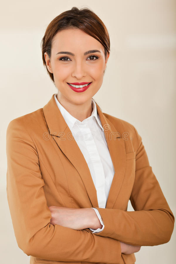 Bedrijfsvrouw die met haar gekruiste wapens glimlachen stock foto's