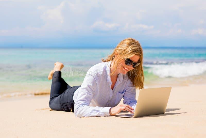 Bedrijfsvrouw die met laptop aan het strand werken stock foto's