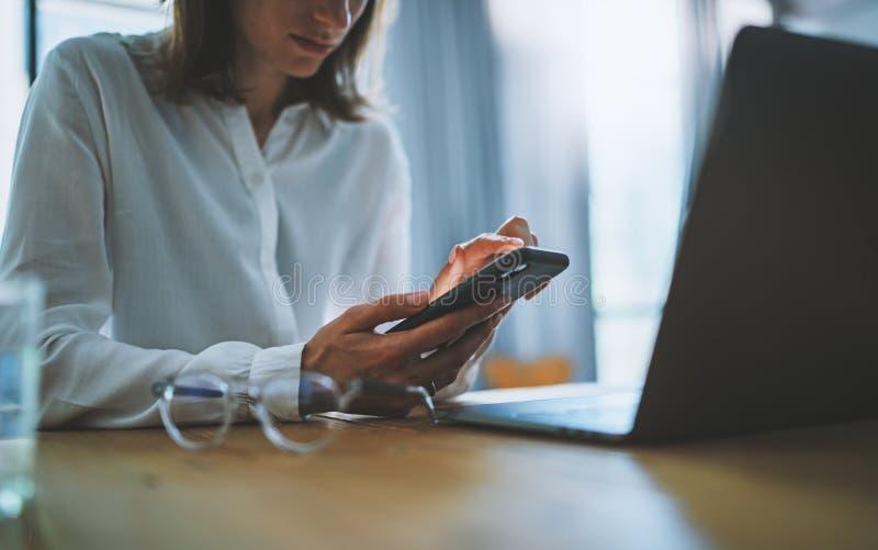 Bedrijfsvrouw die mobiele telefoon met behulp van bij werkdag in bureau Vage achtergrond Bedrijfstechnologiemededelingen stock foto's