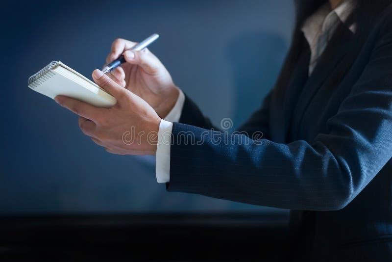 Bedrijfsvrouw die nota's in document op donkerblauwe achtergrond nemen royalty-vrije stock afbeeldingen