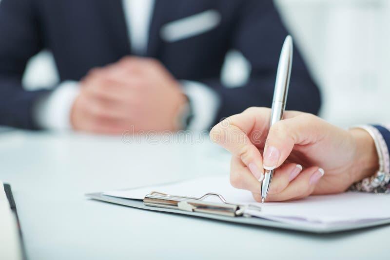 bedrijfsvrouw die nota's maken op het bureauwerk Bedrijfsbaanaanbieding, financieel succes, accountantconcept stock fotografie