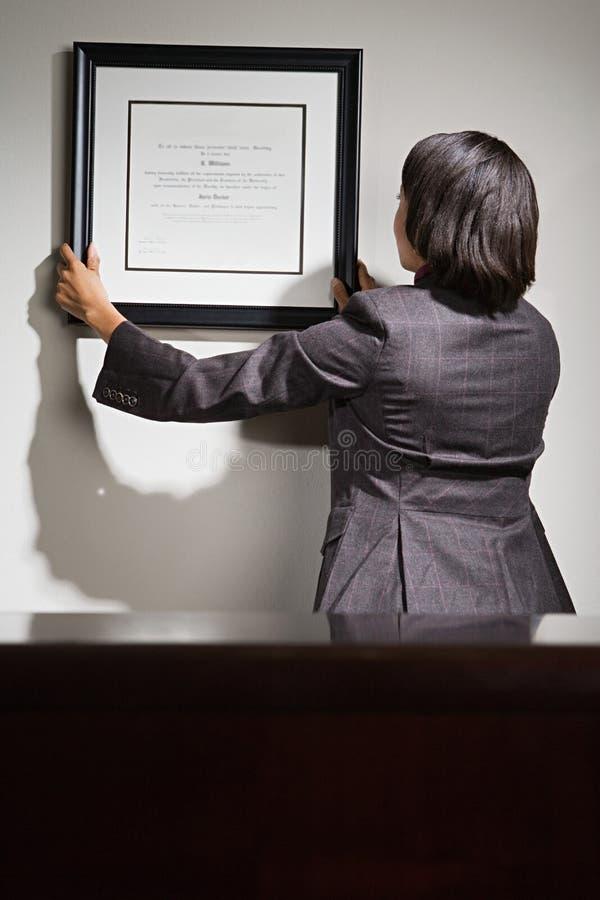 Bedrijfsvrouw die ontworpen certificaat hangen royalty-vrije stock afbeelding