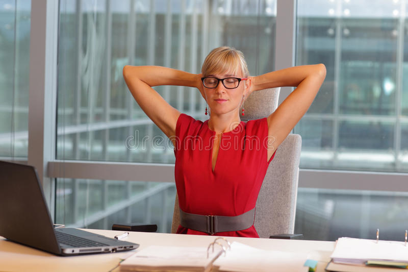 Bedrijfsvrouw die in oogglazen hals ontspannen stock afbeeldingen