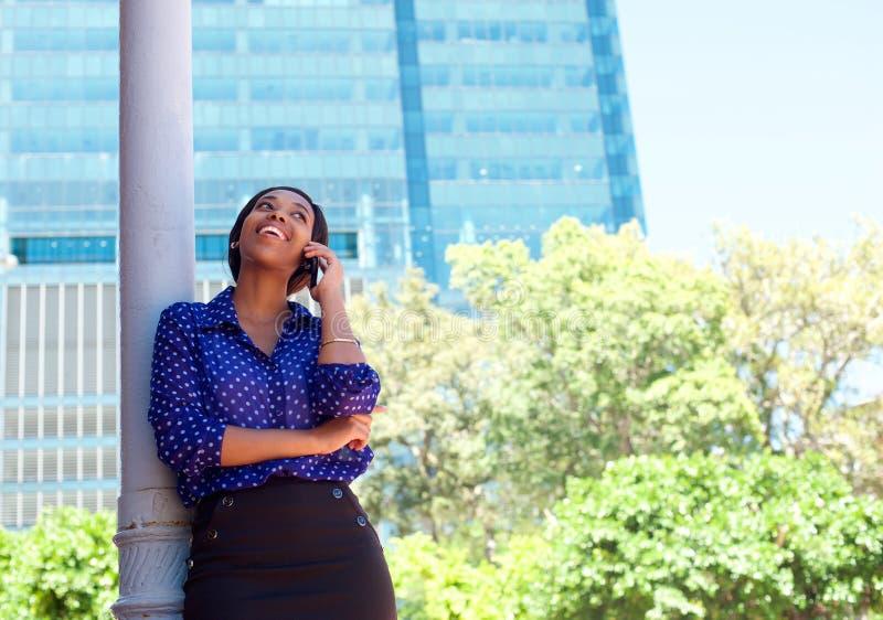 Bedrijfsvrouw die op celtelefoon lachen buiten de bureaubouw royalty-vrije stock afbeeldingen