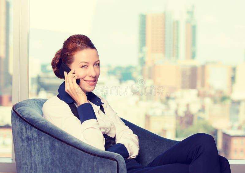 Bedrijfsvrouw die op mobiele telefoon spreken die in leunstoel door het bureauvenster situeren royalty-vrije stock foto's