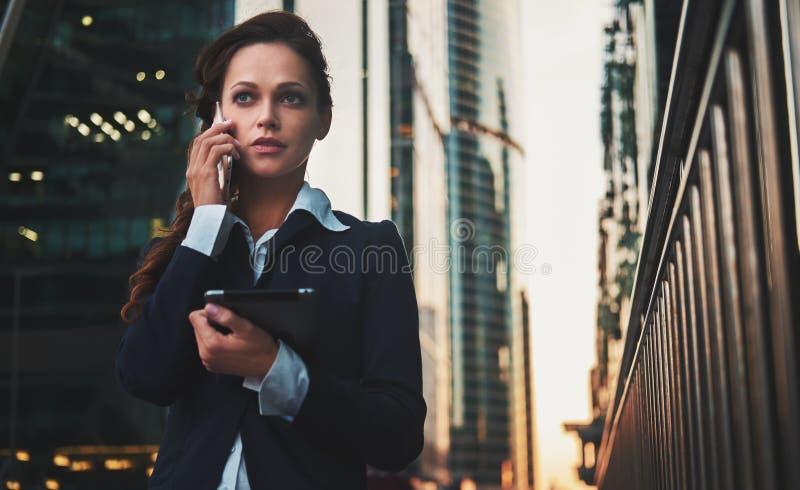Bedrijfsvrouw die op smartphone op de straat spreken stock afbeeldingen
