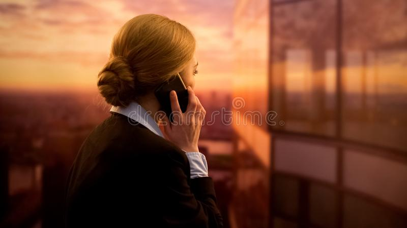 Bedrijfsvrouw die project op telefoon bespreken, die zich op het terras van het bureaucentrum bevinden stock afbeeldingen