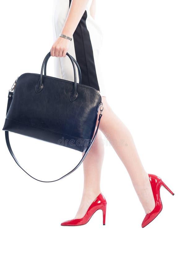 Bedrijfsvrouw die rode schoenen dragen en zwarte handtas houden royalty-vrije stock foto