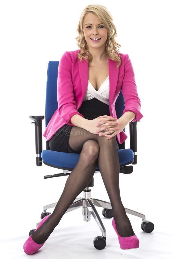 Bedrijfsvrouw die Roze Zitting als Bureauvoorzitter dragen royalty-vrije stock foto's